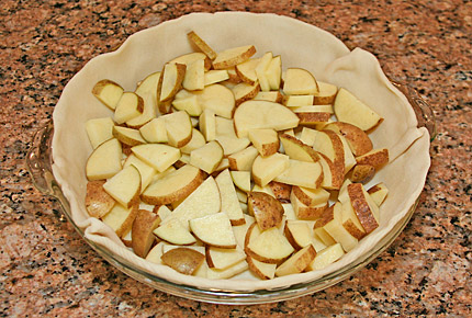 Photo of pie preparation, showing bottom layer of sliced potatoes.